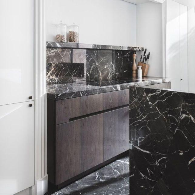 Une cuisine en marbre noir et bois foncé