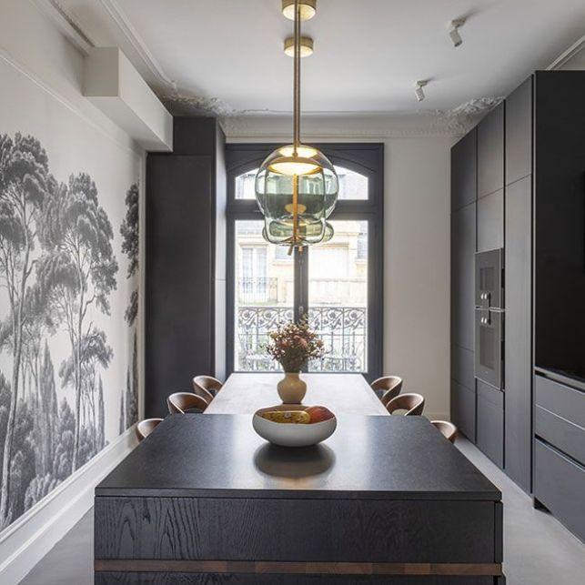 Une cuisine noire et blanche décorée avec un papier peint panoramique