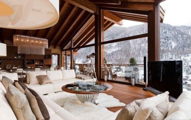 Magnifique salon avec vue panoramique sur la montagne enneigée DR