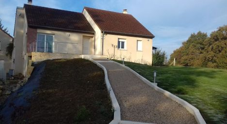 Murets en pierre reconstituée, délimitant l'allée vers l'entée de la maison