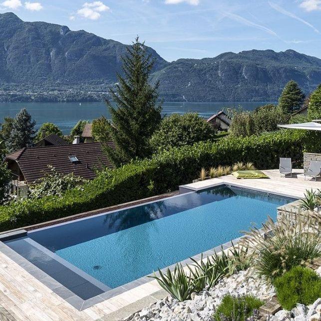 La piscine avec terrasse en bois est contemporaine et design