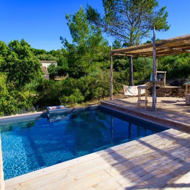 La terrasse de cette piscine en bois s'intègre dans le paysage provençal rustique