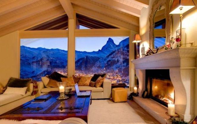 Salon chaleureux avec cheminée et vue sur les montagnes DR