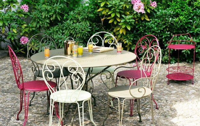 Ce petit salon de jardin comportant une table et six chaises en fil acier allie tradition et confort. © Fermob