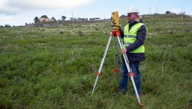 Un géomètre effectuant le bornage d'un terrain