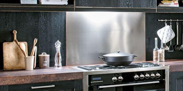 Une crédence de cuisine en inox installée au dessus du plan de cuisson